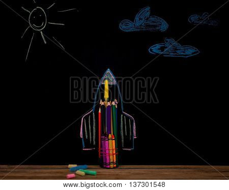 Back to school black background the missile made with pencils drawing with crayons school