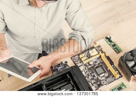 Man using tablet pc during the computer repair.