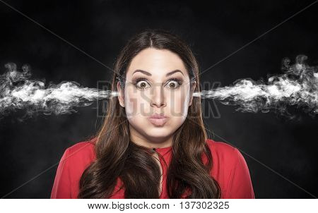 Smoke from the ears of a woman on a dark background. Overvoltage - concept.