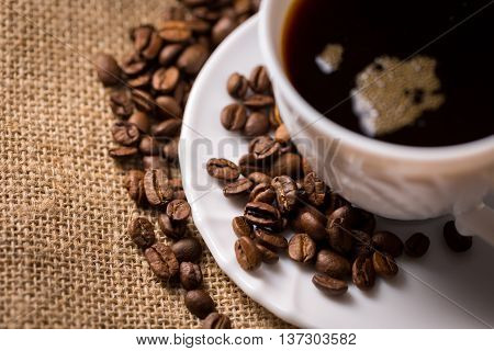 White cup of coffee with saucer and coffeebeans on linen material closeup cutted view from above.