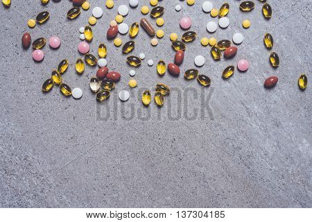 Overhead shot of colorful pills on stone table