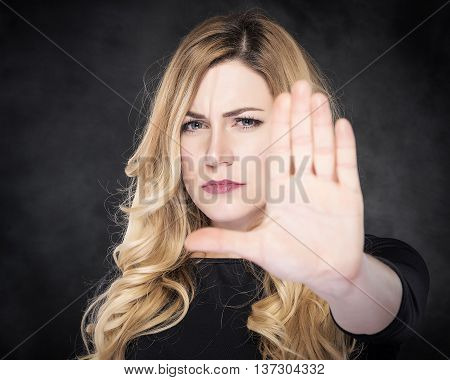 Girl shows stop sign - extended hand. On dark background.
