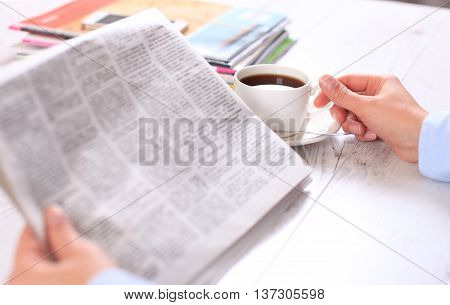 Close-up of female hand on cup of coffee during reading of newspaper