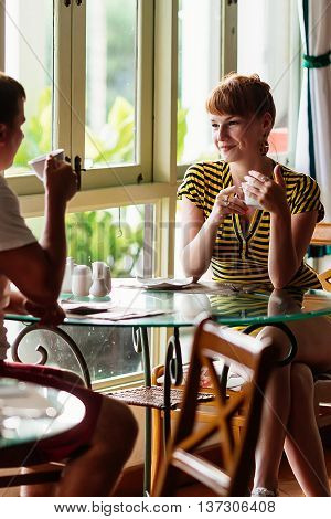The girl sitting next to a guy in a cafe by the window and holding a Cup of tea looking at each other and engaged in dialogue
