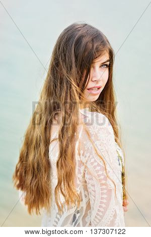 Closeup of beautiful young woman with long blonde hair at the beach in summer. Mild retouch, no filter, natural light.
