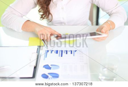 Close-up of young businesswoman hands working with touchpad