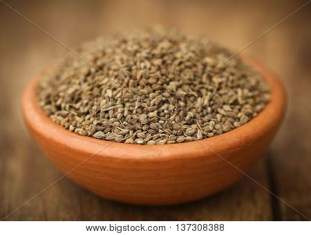 Ajwain seeds in pottery on wooden surface