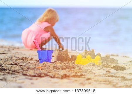 kids toys and little girl building sandcastle on beach