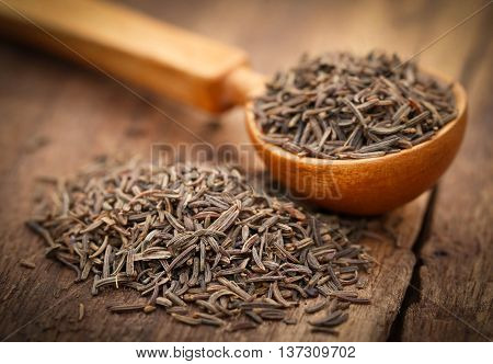 Caraway seeds in a spoon on wooden surface