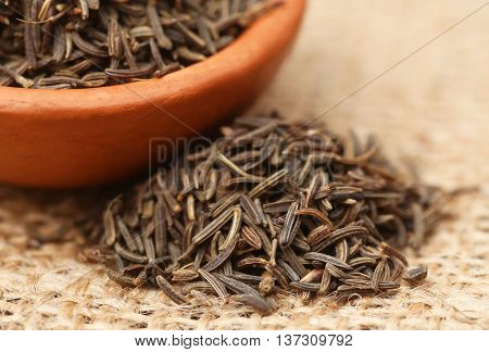 Caraway seeds in a bowl on jute