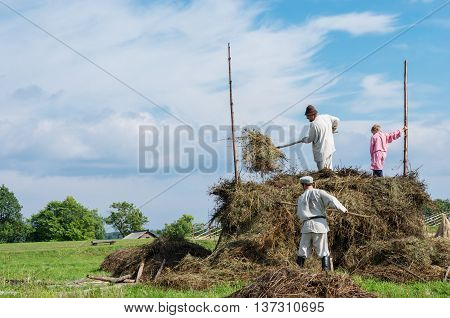 KIZHI RUSSIA - AUG 07 2015: People in national costumes work in the field on the island Kizhi Rusia