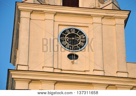 Fragment of St. Francis Xavier Church in Baroque style in Grodno Belarus. Tower with old clock 15th century at sunset.