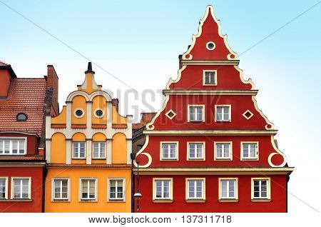 The front facade of two old buildings of red and yellow color with decor in Wroclaw, Poland.
