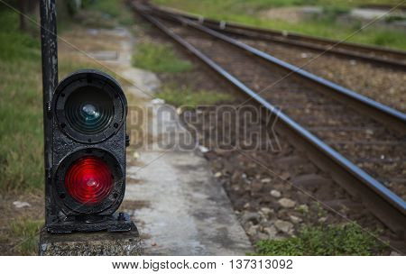 Red semaphore near railway in a developing country. Soft focus.