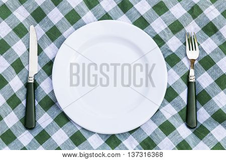 Knife white plate and fork on green picnic tablecloth. Flat lay