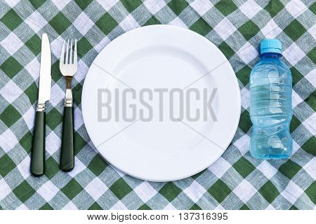 Knife bottle of water white plate and fork on green picnic tablecloth. Flat lay