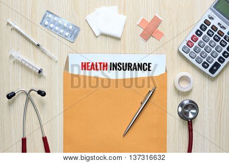 Top view of Health Insurance with letter envelope stethoscope hypodermic syringe plaster gauze medicine tape and calculator.