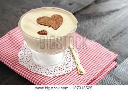 tiramisu dessert in a bowl decorated with a heart of cocoa