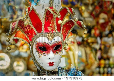 Typical vintage venetian red and golden mask, symbol Annual carnival, in souvenir shop on a street of Venice, Veneto, Italy.