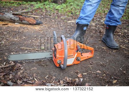 Chainsaw lying on the ground at the feet of men in rubber boots