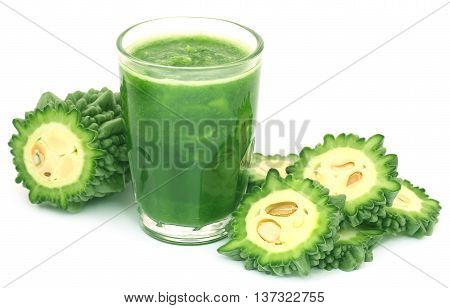 Herbal juice of green momodica in a glass with sliced vegetable