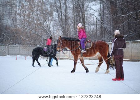 Two girls riding on horses with instructors at the equestrian site in winter