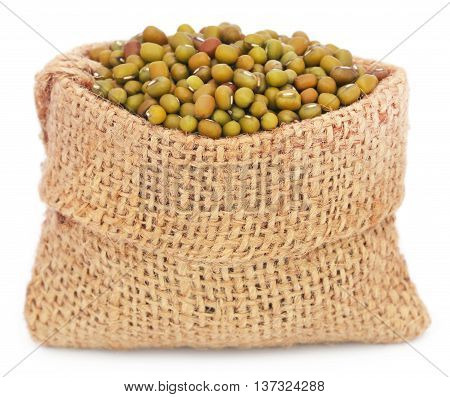 Mung beans in jute bag over white background