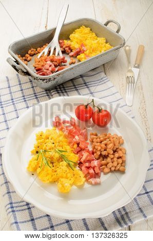 british breakfast with scrambled eggs on a plate smoked bacon cubes baked beans fresh tomatoes rosemary