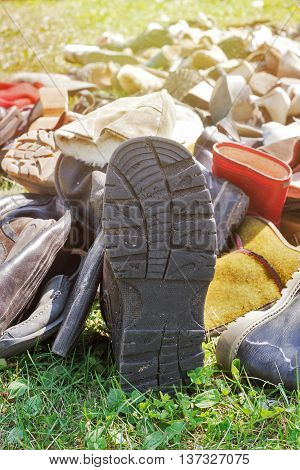 pile of old vintage shoes on the grass