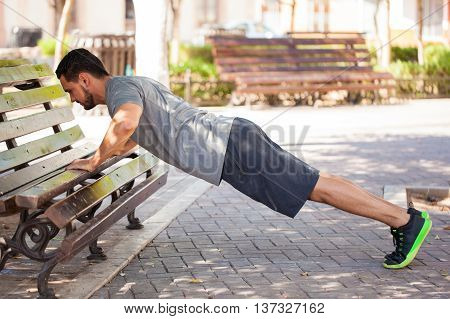 Man Doing Push Ups Outdoor In A Park Bench