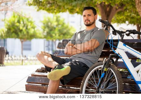 Male Cyclist Sitting In A Park Bench