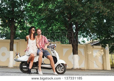 Hipster young couple smiling embracing while sitting on a white scooter on a summer day on trees background outdoors with copy space