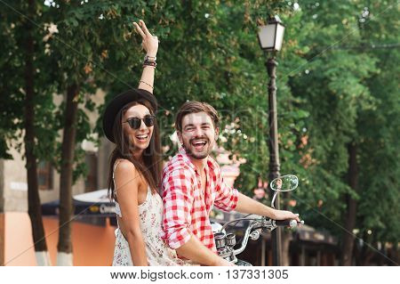 Back view of happy young couple wearing stylish clothes sitting on scooter, posing and smiling on a summer day