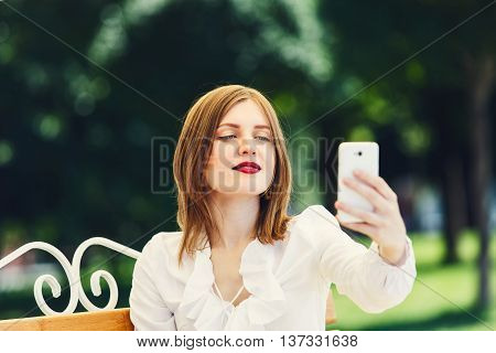 Selfie in the park. Girl or young woman in white blouse makes selfie with tablet. Female student makes photo for internet