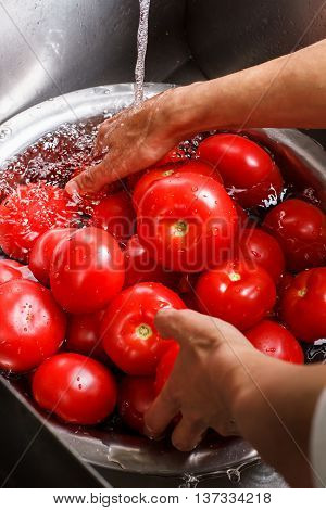 Hands wash tomatoes in basin. Water flowing on red tomatoes. Dietary meals make you healthy. Vegetables of high quality.