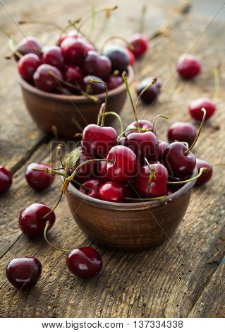 Ripe cherries in a clay bowl on a shabby wooden background