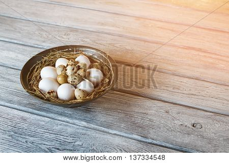 Chicken and quail eggs. Uncooked eggs in a bowl. Protein and cholesterol. Ingredients for tasty omelet.