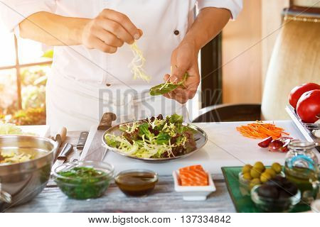 Male hands make salad. Salad plate on cooking board. Don't distract the cook. Need more ingredients.