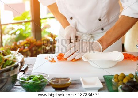 Man's hands touch raw fish. White bowl on cooking board. Chef of top class restaurant. Cook prepares special meal.