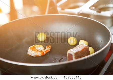 Shrimp on black frying pan. Piece of fish and potatoes. Seafood needs thermal processing. Few minutes and it's ready.