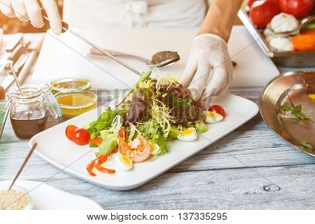 Hands with knife make salad. Salad plate on wooden surface. Salad with frisee and shrimp. Boiled eggs and sliced tomatoes.
