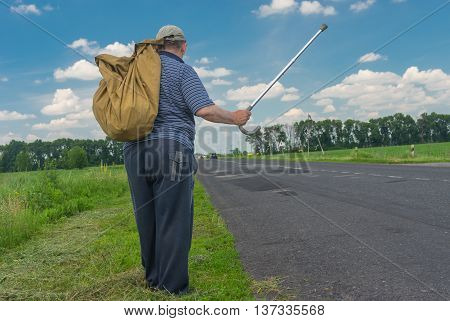 Senior man with sack standing on a roadside holding walking stick up