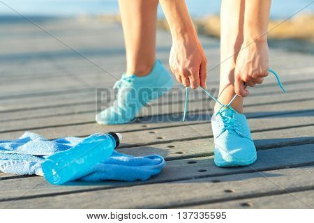 Running shoes - woman tying shoe laces. Closeup of female sport fitness runner getting ready for jogging outdoors on waterfront in summer