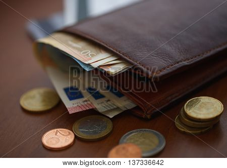 Brown leather wallet with euro money inside and coins credit cards near it