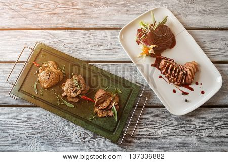 Pieces of meat and herbs. Meat dishes on wooden background. Tasty dishes of european cuisine. Duck breast and meat medallions.