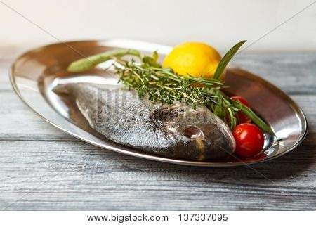 Raw fish on a plate. Lemon and raw fish. Fresh dorado fish with herbs. Ingredients for seafood meal.