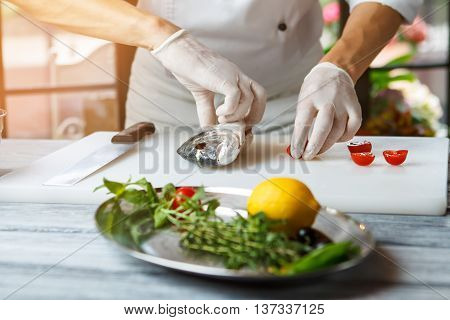 Man's hands touching raw fish. Sliced tomatoes and raw fish. Dorado fish on cooking board. Chef starts preparing a dish.