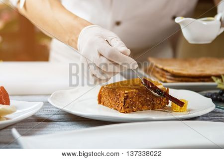 Hand with spoon beside cake. Piece of cake on plate. Chef decorating honey cake. Last steps in preparing dessert.