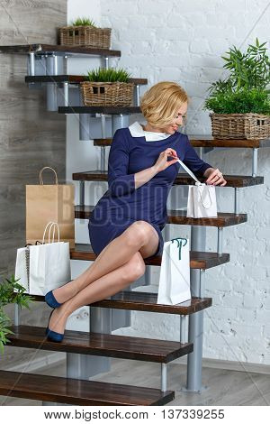 Young Blond Elegant Woman Unpacking Her Shopping Bags On The Stairs