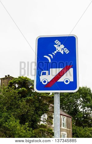 Blue sign showing lorry or HGV with red line through it and a satellite to warn that the road is unsuitable for lorries and not to trust sat-nav.